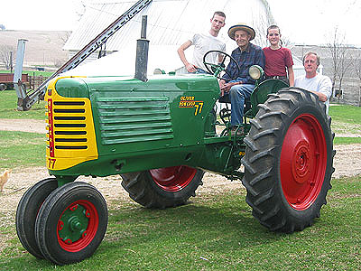 Joseph, Wayne, Daniel, and Russ pose by the newly-restored Oliver 77 tractor, used on the farm since it was purchased new in 1951.